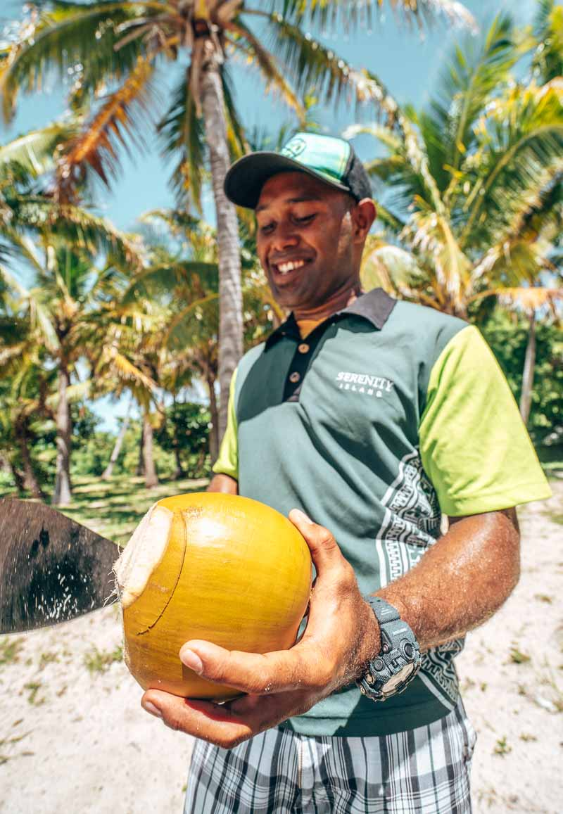 cutting coconuts at serenity island fiji