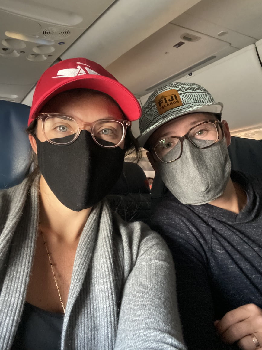 masked couple on airplane